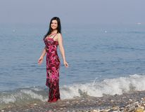 Vrouw in roze kleding bij het overzeese strand royalty-vrije stock foto's