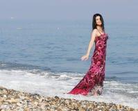 Vrouw in roze kleding bij het overzeese strand stock afbeeldingen