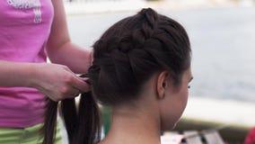 Vrouw in roze overhemds wevende vlecht aan jong donkerbruin meisje hairstyle De zomer stock videobeelden