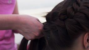 Vrouw in roze overhemds wevende vlecht aan jong donkerbruin meisje hairstyle Manier stock videobeelden