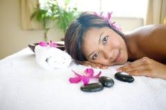 vrouw rustgevend op het bed van de massagetherapie stock foto's