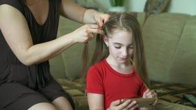Vrouw ` s hands do hairstyle voor haar weinig dochter Een vrouw vlecht haar voor haar dochter stock video