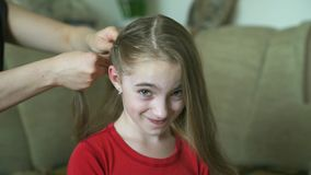Vrouw ` s hands do hairstyle voor haar weinig dochter Een vrouw vlecht haar voor haar dochter stock footage