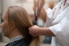 Vrouw in salon en kapper met een hairdryer stock fotografie