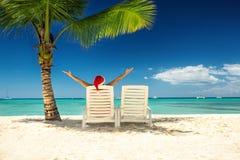 Vrouw in santa` s hoed het ontspannen op tropisch strand Stock Foto's