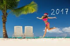 Vrouw in santa` s hoed het ontspannen op tropisch strand stock afbeelding