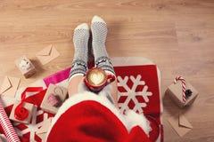 Vrouw in santahoed het drinken cappuccinokoffie en het zitten op de houten vloer Close-up van vrouwelijke benen in warme sokken m royalty-vrije stock afbeeldingen
