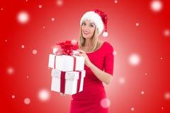Vrouw in santahoed het stellen met giftdozen over de rode winter backgr Stock Afbeeldingen