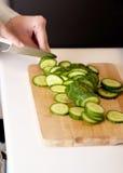 Vrouw in scherpe komkommer op keukenraad. Royalty-vrije Stock Afbeelding