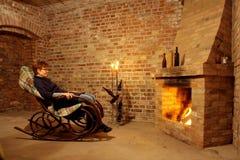 Vrouw in schommelstoel door de open haard met candl royalty-vrije stock afbeeldingen