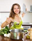 Vrouw in schort kokende soep in keuken Stock Fotografie
