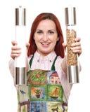 Vrouw in schort met zout en peper Stock Afbeelding