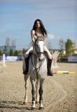 Vrouw schrijlings op een paard Stock Foto