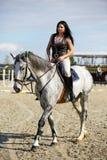 Vrouw schrijlings op een paard Stock Fotografie