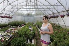 Vrouw in serre van bloemen stock foto's