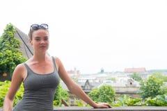 Vrouw in sexy vest in Krakau, Polen Sensuele vrouwentribune op cityscape op witte hemel Het zwerflustavontuur en ontdekt Vakantie stock afbeelding
