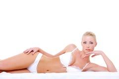 Vrouw in sexy witte lingerie die op het bed ligt Royalty-vrije Stock Afbeeldingen