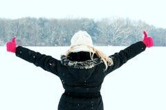 Vrouw in sneeuw die haar rug tonen en bos met omhoog duimen onder ogen zien Royalty-vrije Stock Foto