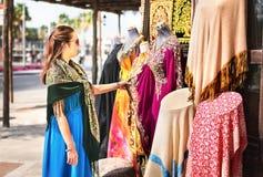 Vrouw in souk Toerist die traditionele Arabische kleding en kleren in opslag of openluchtmarkt bekijken stock fotografie