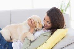 Vrouw spelen met puppy terwijl het liggen op bank Stock Fotografie