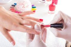 Vrouw in spijkersalon die manicure door schoonheidsspecialist ontvangen Close-up die van vrouwelijke hand op witte handdoek ruste stock afbeelding