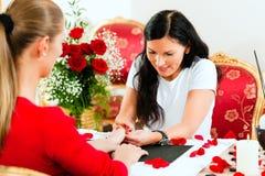 Vrouw in spijkersalon die manicure ontvangt Stock Foto's