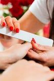 Vrouw in spijkersalon die manicure ontvangt Royalty-vrije Stock Afbeeldingen