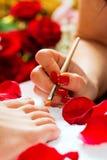 Vrouw in spijkerstudio die pedicure ontvangt Stock Afbeeldingen