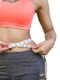Vrouw in sportbustehouder die haar die lichaam met band meten op wit wordt geïsoleerd Stock Foto