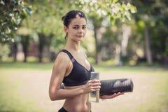 Vrouw in sporten die holdingsfles van water en yogamat kleden Stock Foto's