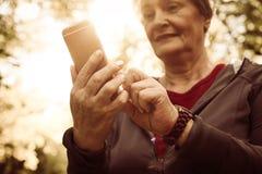Vrouw in sporten die in park het typen op slimme telefoon kleden F royalty-vrije stock afbeelding