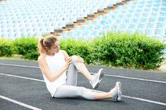 Vrouw in sportkleding die aan kniepijn lijden stock foto's