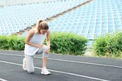 Vrouw in sportkleding die aan kniepijn lijden royalty-vrije stock afbeelding