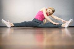 Vrouw in sportkleding het uitrekken zich benen Royalty-vrije Stock Foto's