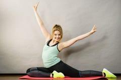 Vrouw in sportkleding het uitrekken zich benen Stock Foto