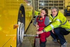 Vrouw, stagiair, die in de busworkshop werken Stock Afbeeldingen