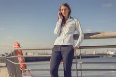 Vrouw status die op mobiel spreken royalty-vrije stock afbeeldingen