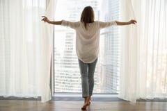 Vrouw status die uit venster het openen gordijnen, achtermening kijken stock foto