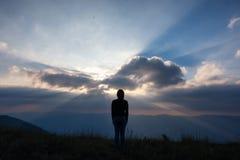 Vrouw status en het letten op zonsondergang met bergenmening in de avond royalty-vrije stock foto