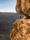 Vrouw stellen die zich op een rots bevinden Royalty-vrije Stock Foto