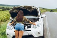 Vrouw in strakke overhemden nieuwe gebroken auto met geopende kap royalty-vrije stock foto's