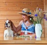 Vrouw in strohoed met hond stock afbeeldingen