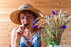 Vrouw in strohoed met komkommer stock afbeeldingen