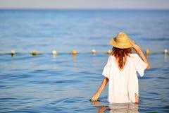 Vrouw in strohoed in zeewater op het strand terug naar ons Royalty-vrije Stock Foto's