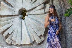 Vrouw in sundress bij de steenmuur Stock Foto
