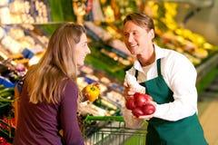 Vrouw in supermarkt en winkelmedewerker Stock Afbeeldingen