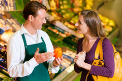 Vrouw in supermarkt en winkelmedewerker Royalty-vrije Stock Foto's