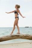 Vrouw in swimmsuitevenwicht op houten boomstam Royalty-vrije Stock Foto's