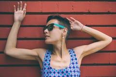 Vrouw tegen de achtergrond van een rode bakstenen muur royalty-vrije stock foto
