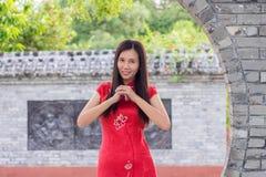 Vrouw in traditionele Cheongsam-het welkom heten gissing tijdens Chinees nieuw jaar Stock Foto's